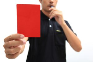Referee showing a red card on white background